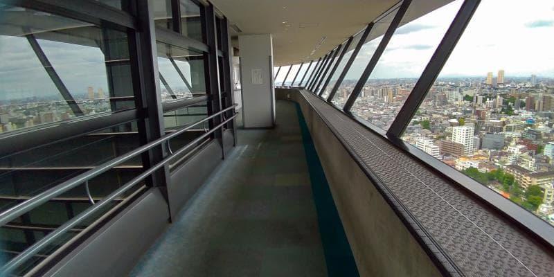 右手に窓と街、左手のガラスにその景色が反射