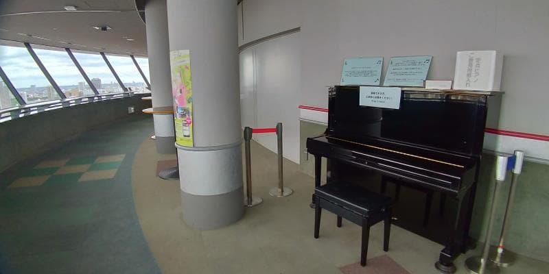 通路に置かれた黒いピアノ
