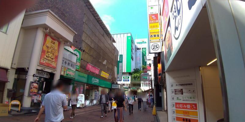 人の往来の多い路地の奥に見える商業施設
