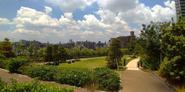 ベンチもある草木のはえた庭園の遠方には都心のビル群。空は雲の多い青空