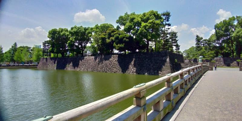 緑に濁った堀にかかる橋。対岸には石垣が見える